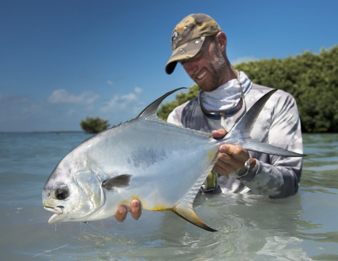 Angler Wil Flack with a permit caught while fly fishing in Belize.